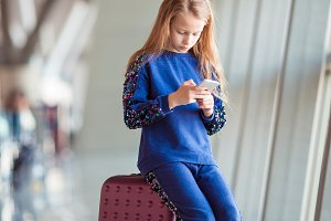 Adorable little girl in airport near big window playing with her phone