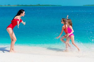 Adorable little girls and young mother on white beach having fun