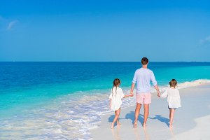 Father and little girls walking on white sandy beach