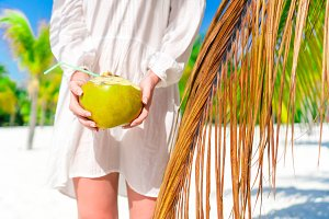 Young woman drinking coconut milk on hot day on the beach. Closeup coconut in female hands