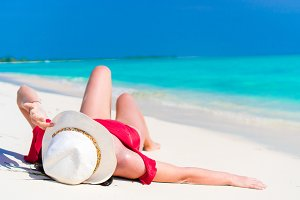 Young beautiful girl lying on snow white tropical beach