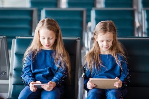 Little adorable girls in airport waiting for boarding playing with laptop