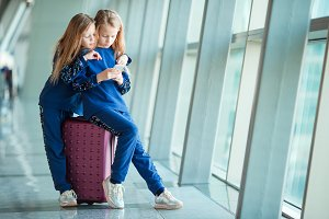 Little adorable girls in airport near big window