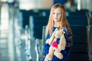 Little adorable girl in airport near big window with her favourite toy ready for travel