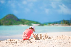 Little adorable girl at tropical beach making sand castle