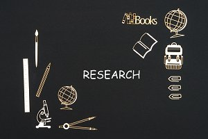 School supplies placed on black background with text research