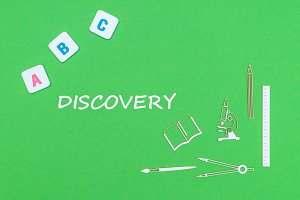 text discovery, from above wooden minitures school supplies and abc letters on green background