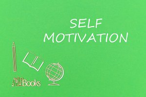 text self motivation, school supplies wooden miniatures on green background
