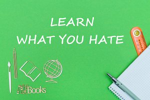 text learn what you hate, school supplies wooden miniatures, notebook on green background