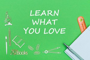 text learn what you love, school supplies wooden miniatures, notebook with ruler, pen on green backboard