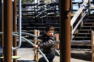 Pretty boy plays on playground
