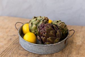 Artichokes and lemons in round metal