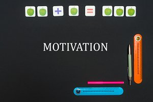 Black art table with stationery supplies with text motivation on blackboard