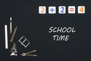 School supplies placed on black background with text school time