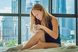 Young woman sitin on bed at home and doing epilation with epilator on legs. On the background of a window overlooking the big city, skyscrapers