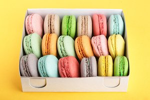 colorful macarons in box on yellow white background closeup