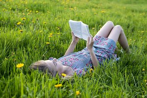 Young girl reading a book in park