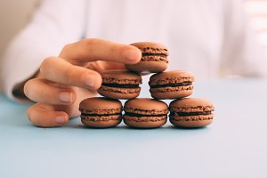Woman placing macarons on heap on blue table