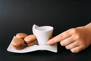 Woman taking set of cup of coffee and macarons against black ba