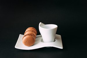 Set of cup of coffee and macarons against black background