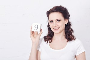 Girl holding number nine.