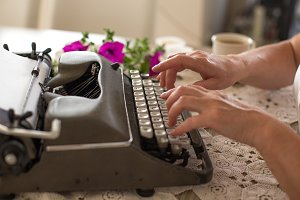 Hands typing on retro typewriter