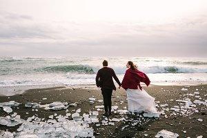 Beautiful Newlyweds is walking on Black Sand Beach, Iceland. Artwork