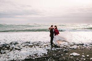 Beautiful Couple is hugging on Black Sand Beach, Iceland. Artwork