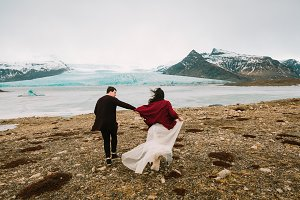 Iceland Wedding in Glacier Lagoon. Bride and groom runs together. Rear view