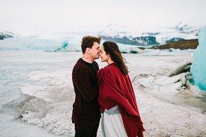 Groom tenderly kissing her beautiful bride in nose. Cheerful newlyweds is hugging in glacier lagoon, Iceland. . Newlyweds