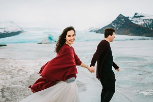 Cheerful Bride and Groom Are Holding Hands And Walking in Glacier Lagoon. Wedding in Iceland