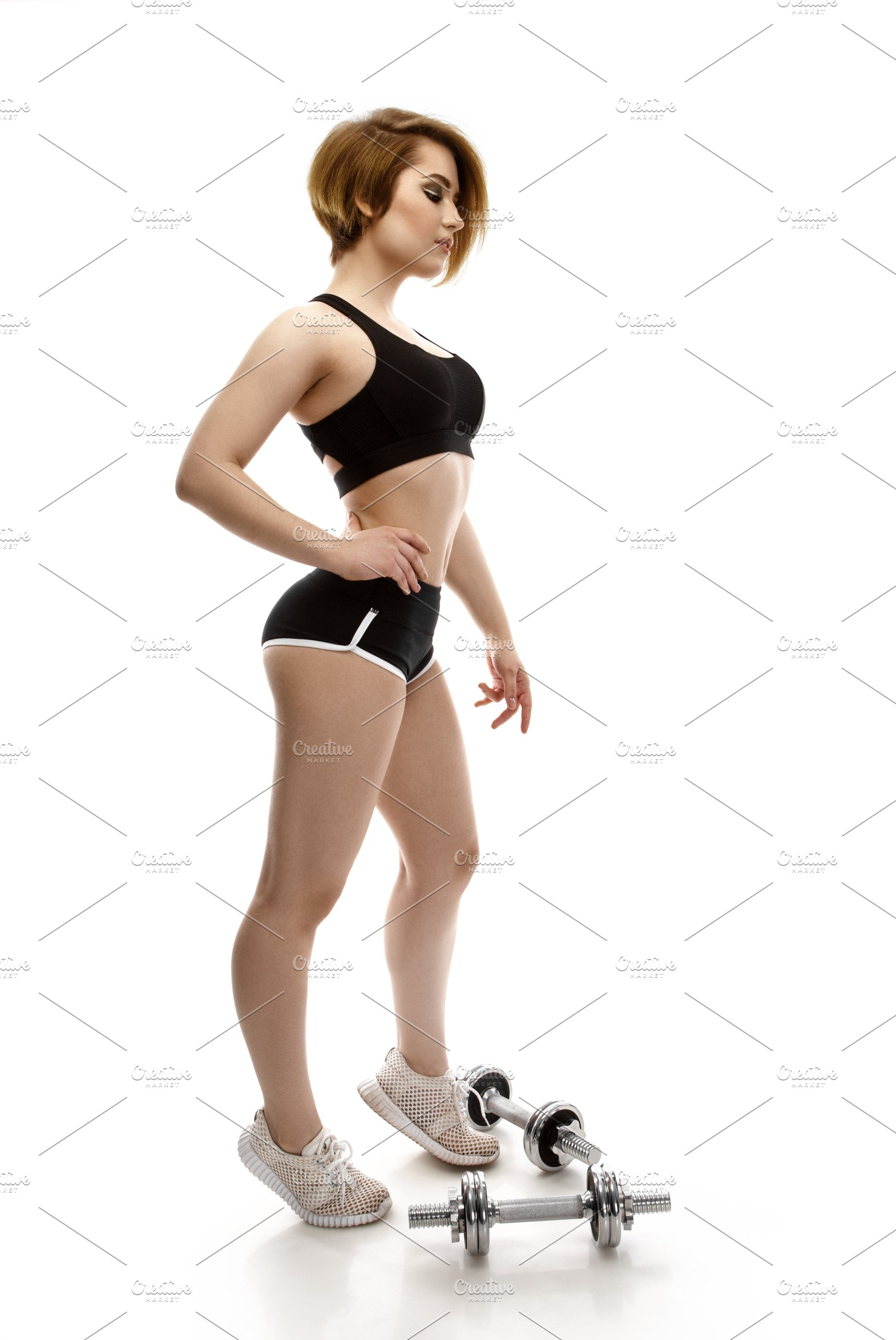 Portrait Of Beautiful Charming Sporty Young Woman With Dumbbells On White