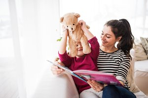 Young mother and a small girl with teddy bear at home, reading a book.