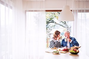 Senior couple eating breakfast at home.