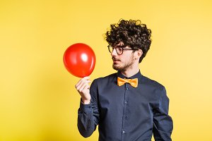 Portrait of a young man with balloon in a studio on a yellow background.