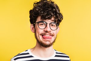 Studio portrait of a young man sticking out his tongue on a yellow background.