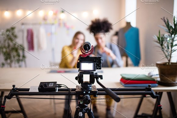 A Camera And A Slider With Women In The Background Startup Business