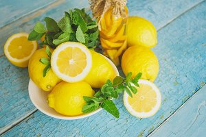 Yellow lemons with mint leaves, wooden background