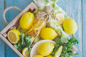 Yellow lemons with mint leaves in the wooden tray