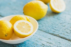 Yellow lemons in the white plate, wooden background