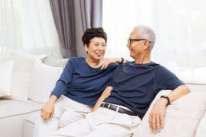 Romantic senior Asian couple laughing and sitting on sofa at home