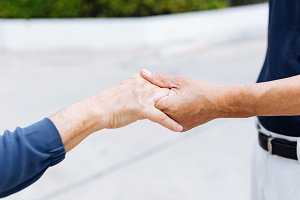 Close up shot of elderly senior couple holding hands and supporting with each other