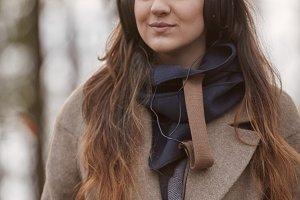 one young girl, looking away, listening to headphones, winter autumn coat, upper body shot.