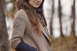 one young woman standing, looking at camera, in forest, wearing winter autumn coat and headphones. side view.