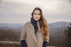 one smirking Caucasian girl outdoors portrait. sky mountains forest behind. wearing winter autumn coat, scarf.