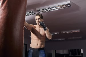 one boxer portrait, adult man, shirtless posing, puching boxing bag, indoors room. wearing boxing gloves, tights.