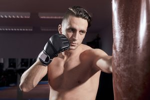 boxer headshot, portrait, face head close up, weaing boxing gloves, punching boxing bag, shirtless, indoors.