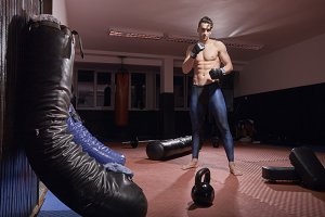 one boxer posing, indoors, boxing bag, fitness boxing equipment, flooring. wearing boxing gloves, tights.