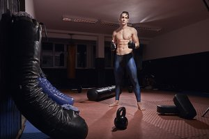 one boxer full lenght portrait, boxing bags, boxing equipment inside room.