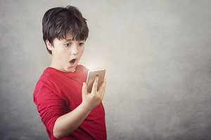 surprised child with a mobile phone